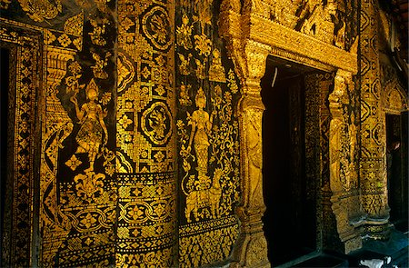 stencil - Laos, Luang Prabang Province, Luang Prabang. Gold-paint stencil murals depicting episodes from the life of legendary King Chanthaphanit adorn the external walls of the sim, or ordination hall, of 16th-century Wat Xieng Thong, among the most famous of Luang Prabang's many Buddhist monasteries. Stock Photo - Rights-Managed, Code: 862-03807831