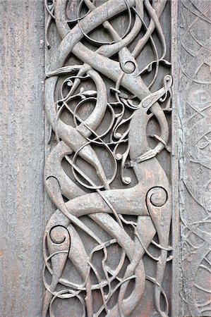stave - Norway, Urnes, Stave Church. A door panel on the outside wall, depicting mythical creatures entwined among foliage. This carving is depicted on the reverse of the 50 ore coin. Stock Photo - Rights-Managed, Code: 862-03808102