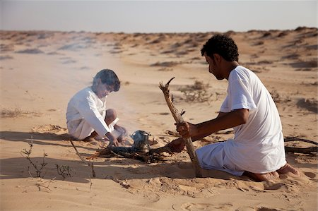 Oman, Wahiba Sands. A Bedouin guide and his son make a fire to make a coffee. Stock Photo - Rights-Managed, Code: 862-03808149