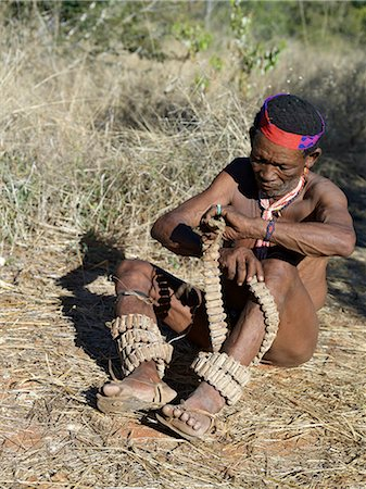 A NIIS hunte gatherer winds strings of rattles round his legs in preparation for a dance.These rattles are made from specially dried cocoons in which are placed tiny chips of stone.The NIIS are a part of the San people, often referred to as Bushmen.They differ in appearance from the rest of black Africa having yellowish skin and being lightly boned, lean and muscular. Stock Photo - Rights-Managed, Code: 862-03820244