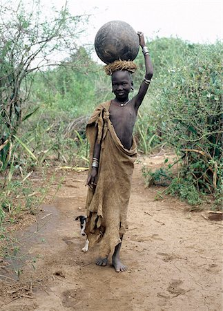 A Mursi girl, accompanied by her dog, carries a large clay pot to collect water from the Omo River. Her earlobes are already pierced and extended, and decorated with round clay discs.She is dressed in skins, attractively decorated with thin stripes.The culture, social organisation, customs and values of the people have changed little. Stock Photo - Rights-Managed, Code: 862-03820367