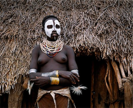 A Karo women stands in the doorway to her hut in the village of Duss. A small Omotic tribe related to the Hamar, who live along the banks of the Omo River in southwestern Ethiopia, the Karo are renowned for their elaborate body painting using white chalk, crushed rock and other natural pigments. In addition to painting her face she has decorated her body with whorls of goat hair tied by leather co Stock Photo - Rights-Managed, Code: 862-03820436