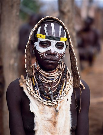 A Karo woman with her face painted in preparation for a dance in the village of Duss. A small Omotic tribe related to the Hamar, who live along the banks of the Omo River in southwestern Ethiopia, the Karo are renowned for their elaborate body painting using white chalk, crushed rock and other natural pigments. She is wearing a goatskin apron and carries a leather belt decorated with cowrie shells Stock Photo - Rights-Managed, Code: 862-03820437