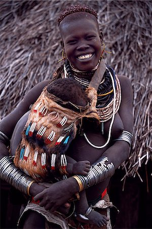 A young Nyangatom woman carries her baby on her hip in an elaborately braided papoose. Her hair has been reddened with a mixture of ochre and animal fat. Typical of her tribe, she wears a calfskin skirt, multiple layers of bead necklaces and metal bracelets and amulets. The Nyangatom or Bume are a Nilotic tribe of semi nomadic pastoralists who live along the banks of the Omo River in south western Stock Photo - Rights-Managed, Code: 862-03820432