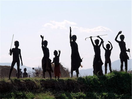 In the late afternoon, a group of Dassanech children wave to passing visitors along a bank of the Omo River in Southwest Ethiopia.The Dassanech speak a language of Eastern Cushitic origin.They live in the Omo Delta and they practice animal husbandry and fishing as well as agriculture. Stock Photo - Rights-Managed, Code: 862-03820478