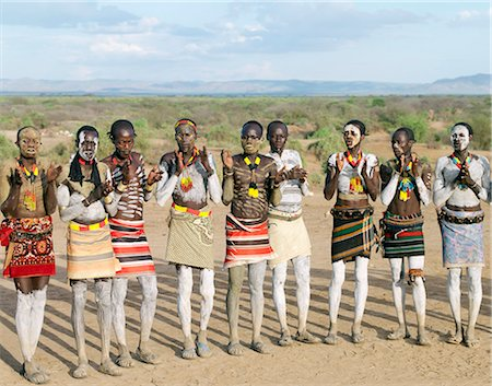 At the start of a dance, Karo men sing and clap in line.The Karo excel in body art. Before dances and ceremonial occasions, they decorate themselves elaborately using local white chalk, pulverised rock and other natural pigments.The Karo are a small tribe living in three main villages along the lower reaches of the Omo River in southwest Ethiopia. Stock Photo - Rights-Managed, Code: 862-03820494