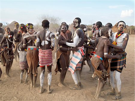 Karo men and girls enjoy a dance.The Karo excel in body art. Before dances and ceremonial occasions, they decorate themselves elaborately using local white chalk, pulverised rock and other natural pigments.The Karo are a small tribe living in three main villages along the lower reaches of the Omo River in southwest Ethiopia. Stock Photo - Rights-Managed, Code: 862-03820495