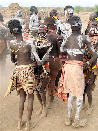 Karo men and girls enjoy a dance.The Karo excel in body art. Before dances and ceremonial occasions, they decorate themselves elaborately using local white chalk, pulverised rock and other natural pigments.The Karo are a small tribe living in three main villages along the lower reaches of the Omo River in southwest Ethiopia. Stock Photo - Rights-Managed, Code: 862-03820496