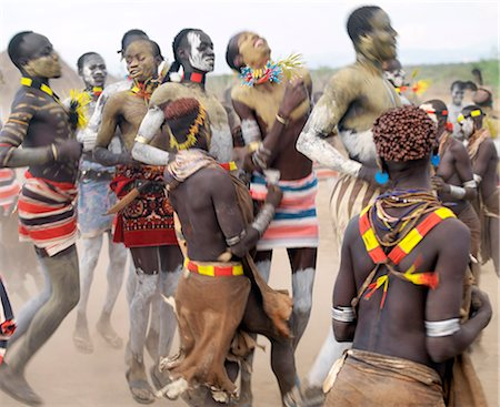 Karo men and girls enjoy a dance.The Karo excel in body art. Before dances and ceremonial occasions, they decorate themselves elaborately using local white chalk, pulverised rock and other natural pigments.The Karo are a small tribe living in three main villages along the lower reaches of the Omo River in southwest Ethiopia. Stock Photo - Rights-Managed, Code: 862-03820497