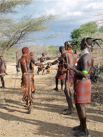 A Hamar woman implores a man to whip her at a Jumping of the Bull ceremony.Female friends and relatives of the initiate are willing whipped with pliable sticks to show their solidarity and love for him. They do not flinch or show any sign of pain.The semi nomadic Hamar of Southwest Ethiopia embrace an age grade system that includes several rites of passage for young men. Stock Photo - Rights-Managed, Code: 862-03820514