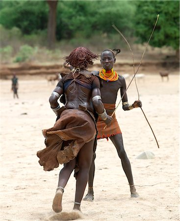 A Hamar woman being whipped by a man at a Jumping of the Bull ceremony.The semi nomadic Hamar of Southwest Ethiopia embrace an age grade system that includes several rites of passage for young men. Stock Photo - Rights-Managed, Code: 862-03820513