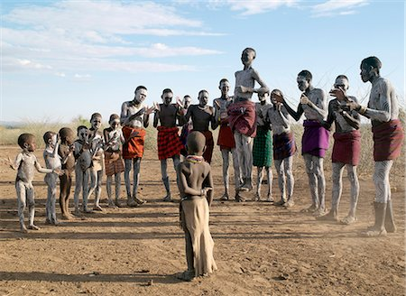 In the late afternoon, Nyangatom villagers enjoy singing and dancing. As groups of men take centre stage to jump high in the air, women and girls sing, clap to a rhythm, and move slowly towards the men. Children enjoy the excitement in the background.The Nyangatom are one of the largest tribes and arguably the most warlike people living along the Omo River in Southwest Ethiopia. Stock Photo - Rights-Managed, Code: 862-03820538