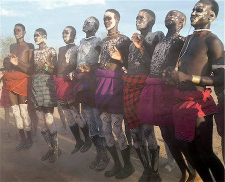 In the late afternoon, Nyangatom villagers enjoy singing and dancing. As groups of men take centre stage to jump high in the air, women and girls sing, clap to a rhythm, and move slowly towards the men. Children enjoy the excitement in the background.The Nyangatom are one of the largest tribes and arguably the most warlike people living along the Omo River in Southwest Ethiopia. Stock Photo - Rights-Managed, Code: 862-03820539