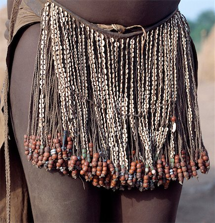The decorated leather apron or skirt of a young Nyangatom girl. The numerous white discs woven into the strands of braided leather are made of ostrich shell.The Nyangatom are one of the largest tribes and arguably the most warlike people living along the Omo River in Southwest Ethiopia. Stock Photo - Rights-Managed, Code: 862-03820547