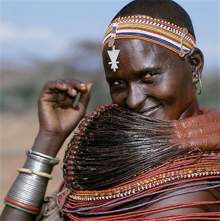 A Samburu woman wearing a mporro necklace, which denotes her married status. These necklaces were once made of hair from giraffe tails but nowadays, the fibres of doum palm fronds, Hyphaene coriacea, are used instead.The red beads after which the necklace is named are wound glass beads made in Venice c.1850. Stock Photo - Rights-Managed, Code: 862-03820644