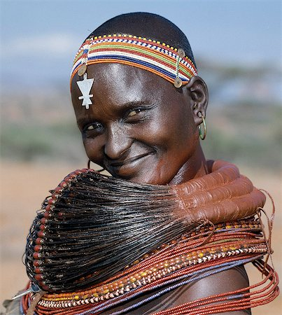 A Samburu woman wearing a mporro necklace, which denotes her married status. These necklaces were once made of hair from giraffe tails but nowadays, the fibres of doum palm fronds, Hyphaene coriacea, are used instead.The red beads after which the necklace is named are wound glass beads made in Venice c.1850. Stock Photo - Rights-Managed, Code: 862-03820645
