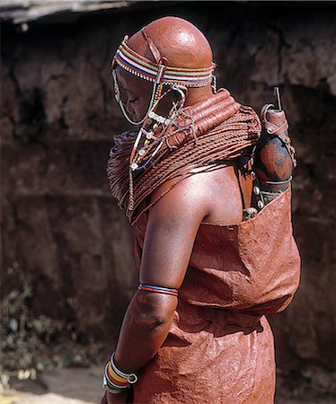 A Samburu bride waits pensively outside her new home until she is enticed in with promises of cattle.Her wedding gown is made of three goatskins, which are well oiled and covered in red ochre.She carries on her back a gourd full of milk and a small wooden jar containing butter.She now wears the mporro necklace of married women. Stock Photo - Rights-Managed, Code: 862-03820649