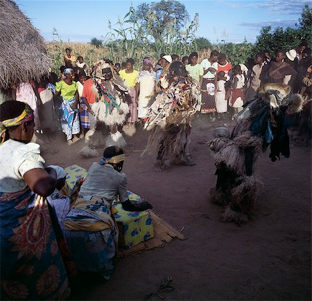 The Chewa people, Malawis largest ethnic group, live on the west side of Lake Malawi. Despite years of missionary influence, they still cling to old beliefs and rituals. For them, death simply means a journey of rebirth into the spirit world.The terrestrial representatives of this other world are grotesquely masked dancers known as Gule Wamkulu. Stock Photo - Rights-Managed, Code: 862-03820882