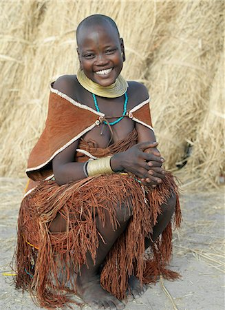 A Datoga woman relaxes outside her thatched house.The traditional attire of Datoga women includes beautifully tanned and decorated leather dresses and coiled brass armbands and necklaces.Scarification of the face is not uncommon among women and girls. Stock Photo - Rights-Managed, Code: 862-03821031