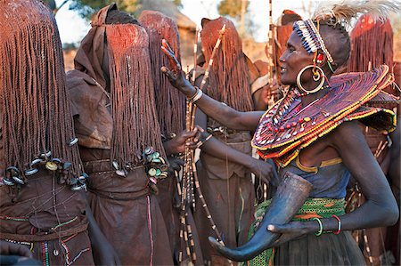 fat african woman - At the start of a Ngetunogh ceremony, the mothers of Pokot initiates will smear animal fat on the boys masks as a blessing. The boys must wear goatskins, conceal their faces with masks made from wild sisal (sansevieria) and carry bows with blunt arrows until this ceremony is over. Stock Photo - Rights-Managed, Code: 862-03888761