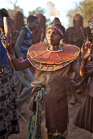 During a Ngetunogh ceremony, the mother of a Pokot initiate sings and dances holding high the cowhorn container she used to smear fat over the masks of her son and other boys as a blessing. Stock Photo - Rights-Managed, Code: 862-03888762