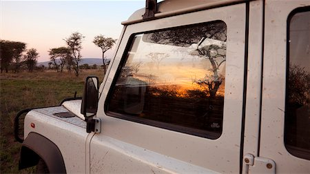 serengeti national park - Tanzania, Serengeti. Sunrise over the bush is reflected in the window of a Land Rover. Stock Photo - Rights-Managed, Code: 862-03890057