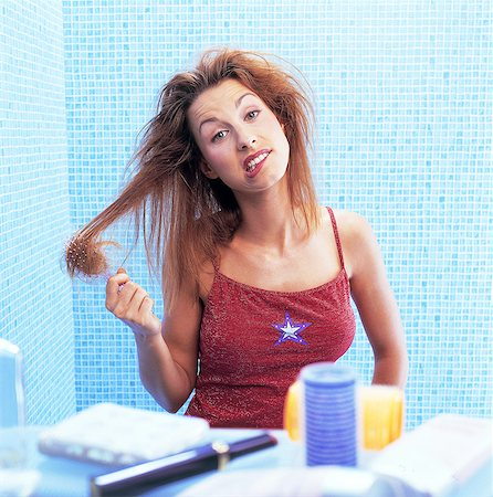 Portrait woman untangling her hair in bathroom Stock Photo - Rights-Managed, Code: 877-06835899