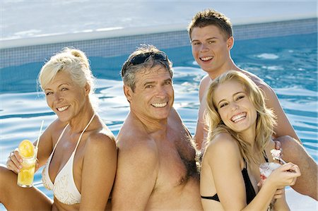 Mature couple and young couple sitting near a pool Stock Photo - Rights-Managed, Code: 877-06832467