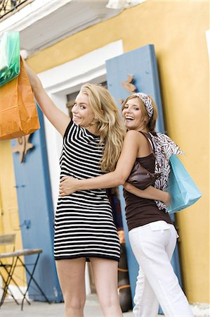 Two young women walking in the street, holding bags Stock Photo - Rights-Managed, Code: 877-06832537