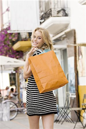 Youn woman in street holding bags Stock Photo - Rights-Managed, Code: 877-06832532