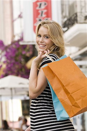 Youn woman in street holding bags Stock Photo - Rights-Managed, Code: 877-06832533