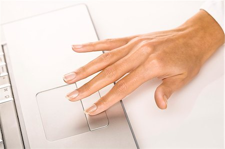 finger holding a key - Woman's hand on a laptop Stock Photo - Rights-Managed, Code: 877-06832557