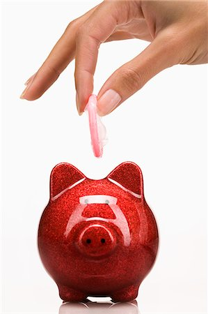 Woman's hand holding a concom above a piggy bank Stock Photo - Rights-Managed, Code: 877-06832584
