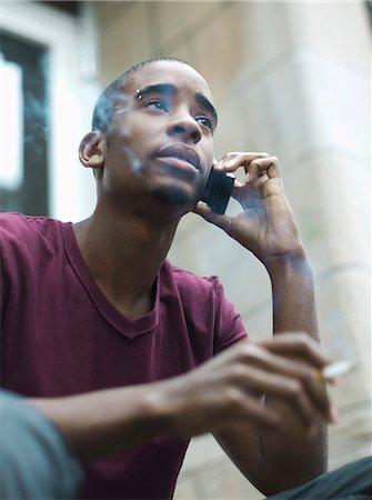 Teenage boy smoking while phoning Stock Photo - Rights-Managed, Code: 877-06833928