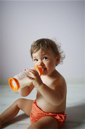 A 15 months old baby girl posing with her baby bottle Stock Photo - Rights-Managed, Code: 877-08031247