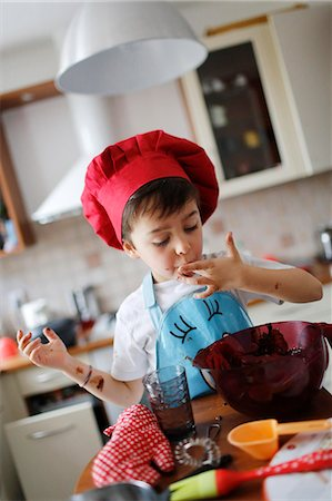A little boy tasted the chocolate cake preparation Stock Photo - Rights-Managed, Code: 877-08031252