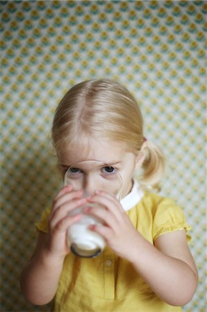 A 2 years old girl posing as she 's drinking a glass of milk Stock Photo - Rights-Managed, Code: 877-08031299