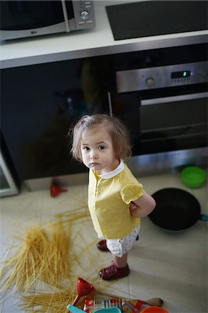 A 2 years old little girl posing in a kitchen in which she made the mess Stock Photo - Rights-Managed, Code: 877-08079194