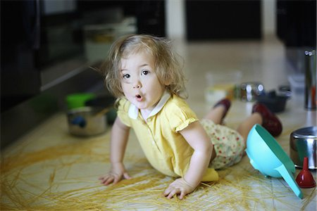 A 2 years old little girl posing in a kitchen in which she made the mess Stock Photo - Rights-Managed, Code: 877-08079198