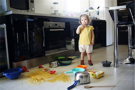 A 2 years old little girl posing in a kitchen in which she made the mess Stock Photo - Rights-Managed, Code: 877-08079190