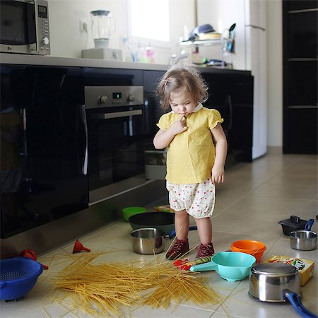 A 2 years old little girl posing in a kitchen in which she made the mess Stock Photo - Rights-Managed, Code: 877-08079192