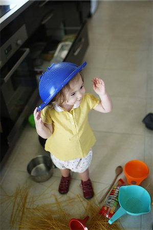 A 2 years old little girl playing in a kitchen in which she made the mess Stock Photo - Rights-Managed, Code: 877-08079193