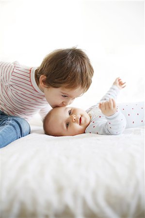 A little boy of 4 years old kissing on the head his baby sister of 10 months Stock Photo - Rights-Managed, Code: 877-08079245