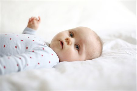 picture - Portrait of a 10 months baby girl lying down on a bed Stock Photo - Rights-Managed, Code: 877-08079246