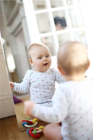 A 10 months baby girl in front of a mirror Stock Photo - Rights-Managed, Code: 877-08079243
