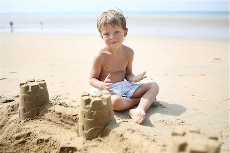 Little boy making a sand castle on the beach Stock Photo - Rights-Managed, Code: 877-08128131