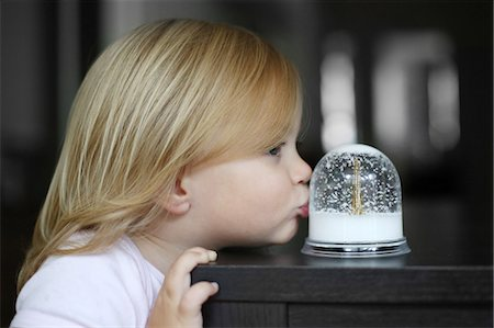 A 2 years old little girl kisses a snow globe Stock Photo - Rights-Managed, Code: 877-08129049