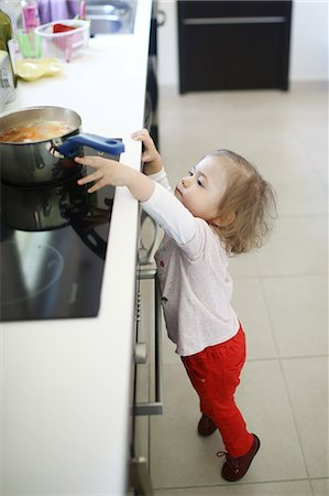 dangerous accident - A 2 years old little girl is about to catch a saucepan on the hob Stock Photo - Rights-Managed, Code: 877-08129098