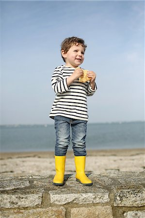 3 years old boy eating a crepe at the beach Stock Photo - Rights-Managed, Code: 877-08129124