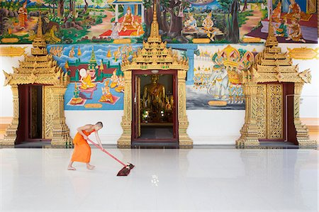 Laos, Vientiane, Buddhist monk cleaning the ground at the entrance of Mixay temple Stock Photo - Rights-Managed, Code: 877-08898112